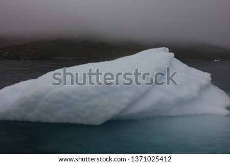 Closeup photo of a melting iceberg in a fjord in Greenland #1371025412