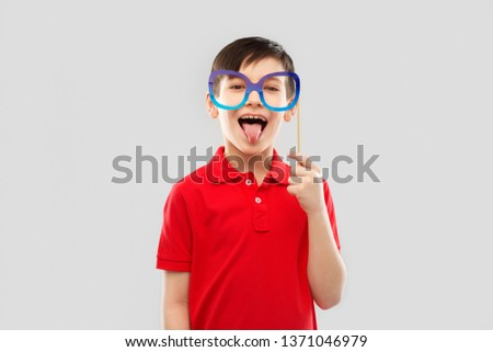 party props, photo booth and childhood concept - happy little boy in red polo t-shirt with big paper glasses showing tongue over grey background