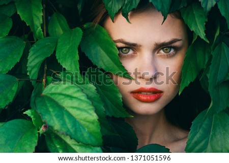 pretty model with make up on face red lips green leaves #1371051596