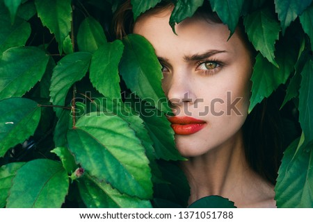 Pretty woman with make up on face green shrub red lips model #1371051788