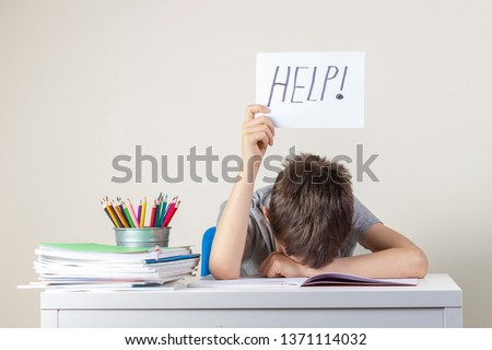 Sad tired frustrated boy sitting at the table with many books and holding paper with word Help. Learning difficulties, education concept. Royalty-Free Stock Photo #1371114032