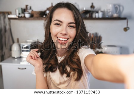 Attractive brunette woman wearing apron taking a selfie while sitting at the kitchen at home