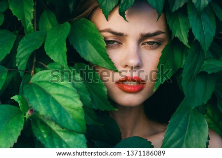 Beautiful female face on among the green leaves of the bush                   #1371186089