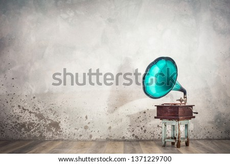 Vintage antique aged aquamarine gramophone phonograph turntable on aged wooden stool front concrete wall background with its shadow. Retro old style filtered photo #1371229700