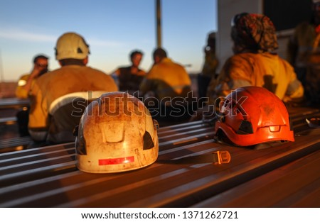 Red rope access miner safety helmet head fall protection place on the table with defocused miners at the background Perth, Australia #1371262721