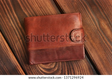 Leather wallet on a wooden background. Royalty-Free Stock Photo #1371296924