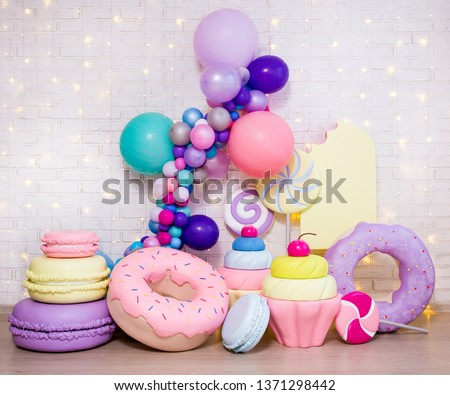 set of huge artificial sweets and pastry decorations over white brick wall background #1371298442