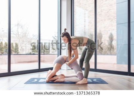 Young female stretching teacher teaches her client how to do stretching exercises for the spine. The concept of individual training with the coach #1371365378