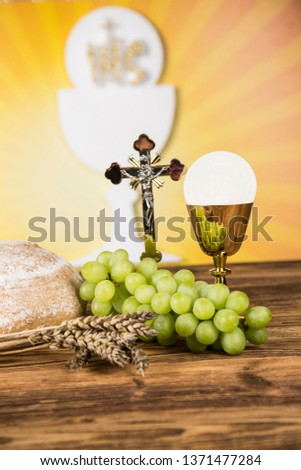 Holy communion a golden chalice with grapes and bread wafers #1371477284