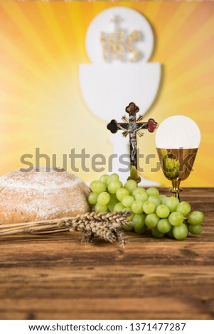 Holy communion a golden chalice with grapes and bread wafers #1371477287