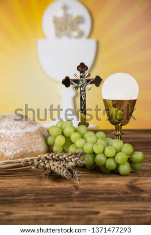 Holy communion a golden chalice with grapes and bread wafers #1371477293