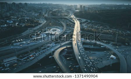 Night Aerial Urban Traffic Road System. Busy Downtown Route Development City Highway Junction Overview. Cityscape Car Motion Transport. Dark Blue Cinematic Filter. Concept Drone Flight Shot Royalty-Free Stock Photo #1371490904
