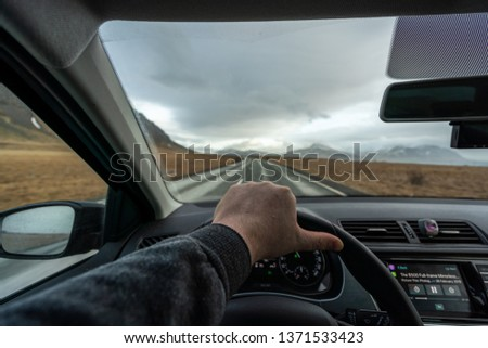 Man driving along the ring road in Iceland, hand on wheel in car in motion.  #1371533423