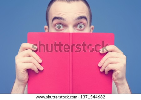 Man reads the book, surprised looks at the camera, open red book or tutorial, close up, copy space, for advertising, slogan, toned