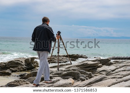 Young man setting up tripod for shooting photography and video making. Travel photography concept. Copy space. #1371586853