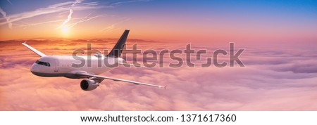 Commercial airplane jetliner flying above dramatic clouds in beautiful sunset light. Travel concept. #1371617360