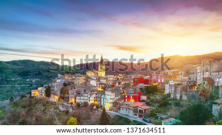 Panorama of the belltower and the village in the valley at early sunrise. Mountain village Novara di Sicilia, Sicily, Italy #1371634511