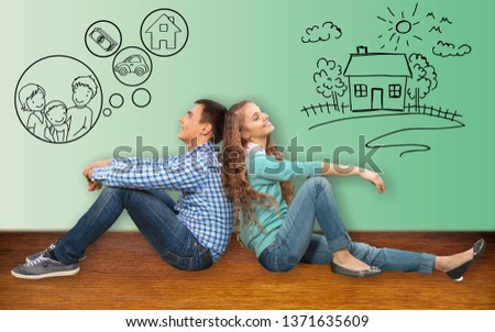 Couple sitting back-to-back dreaming with doodle pictures on wall #1371635609