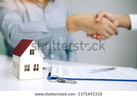 Home sales agents and buyers work on signing new homes and shaking hands. #1371692318