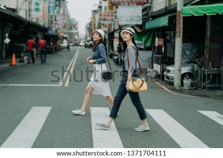 two happy female friends travelers with bags crossing street together outdoor sunny day in china town. japanese lady travel in chinese city walking on zebra cross in urban. girl wear hats look at sky. #1371704111