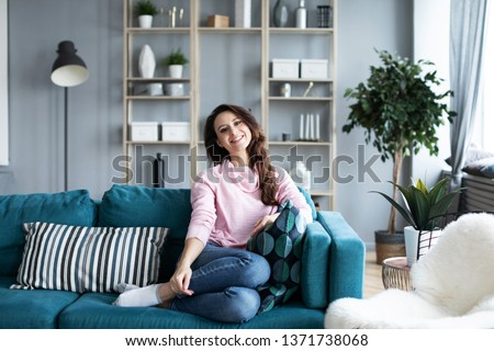 Beautiful smiling woman at home on the sofa. Portrait of a positive girl indoors. #1371738068