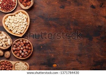 Various nuts selection: peanuts, hazelnuts, chestnuts, walnuts, pistachio and pecans on wooden table. Top view with space for your text #1371784430