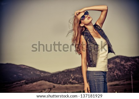 Beautiful young woman posing on a road over picturesque landscape. #137181929