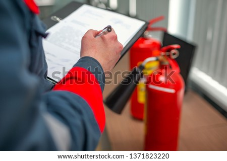 Engineer Professional are Checking A Fire Extinguisher Using Clipboard or checking Industrial fire control system,Fire Alarm controller, Fire notifier.System ready In the event of a fire. #1371823220
