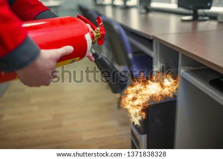 A man practices how to use a powder type extinguisher  in the office. The rescuer puts out the computer #1371838328