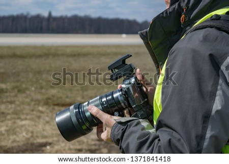 Domodedovo airport / Russia - April 7 2019: A male photographer in winter jacket and green vest holding digital photocamera in the outdoors on a sunny day. #1371841418