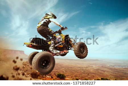 Quad bike in dust cloud, sand quarry on background. ATV Rider in the action. #1371858227