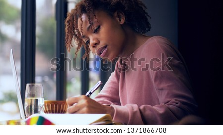 pretty young African woman writing indoor Young Black female college student study indoor by the window doing homework #1371866708