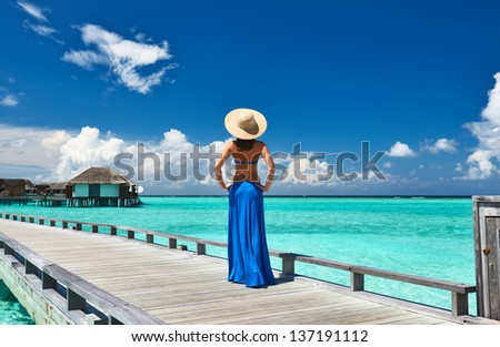 Woman on a tropical beach jetty at Maldives #137191112
