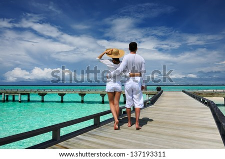 Couple on a tropical beach jetty at Maldives #137193311