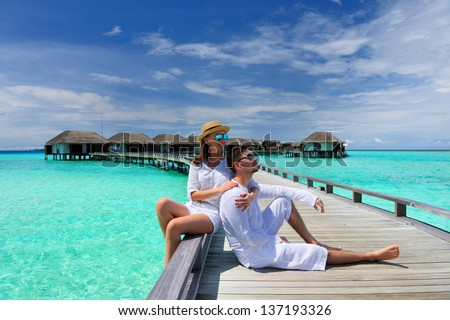 Couple on a tropical beach jetty at Maldives #137193326