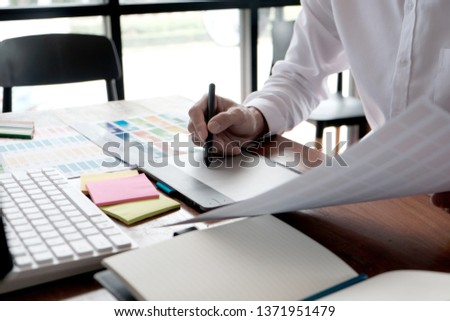 Graphic designer working on digital tablet. artist drawing on graphic tablet and Color swatch samples #1371951479