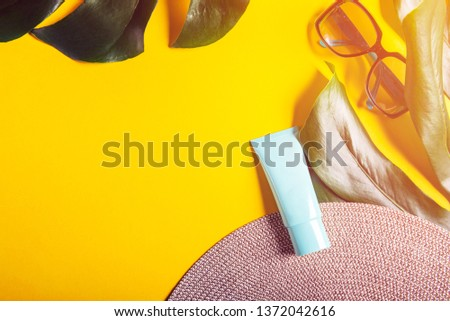 Sunscreen product on yellow background, flat lay. Spring and summer protection against the Sun #1372042616