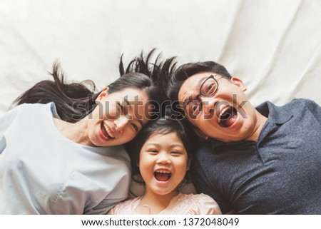 Happy Asian family laying on bed in bedroom with happy and smile, top view #1372048049