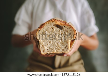 Female baker standing at bakery and holding fresh bread.  Close up of a female baker holding a bread loaf in bakery. #1372115126