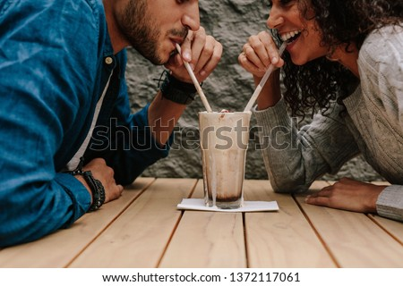Happy young couple in love at cafe drinking a milkshake from same glass. Young man and woman enjoying a chocolate shake on table. #1372117061