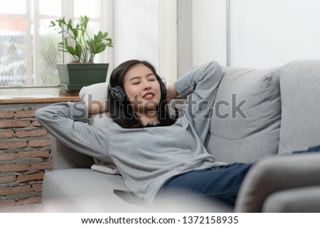 Relaxed asian woman in headphones listening music and laying down on the sofa. #1372158935