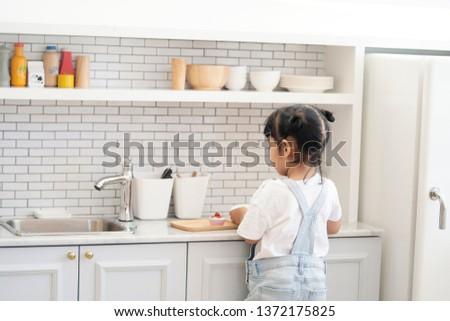 Kid in the kitchen. Child prepare the food in the modern kitchen. #1372175825