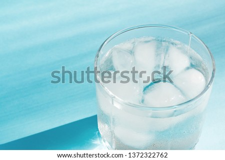 Close up of pure water with ice in transparent glass and sun glare on blue  background. #1372322762