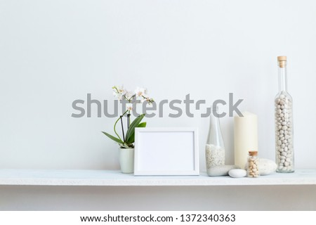 Modern room decoration with picture frame mockup. Shelf against white wall with decorative candle, glass and rocks. Potted orchid plant.