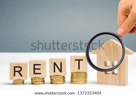 Magnifying glass, wooden blocks with the word Rent, coins and a miniature house. The concept of renting housing and real estate. The cost of a rented home or apartment. Saving money. Rental. Royalty-Free Stock Photo #1372353404