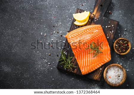 Fresh Salmon fish. Uncooked salmon fillet with ingredients for cooking on black stone table. Top view with copy space. #1372368464