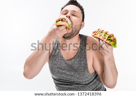 overweight man in tank top eating tasty hot dog isolated on white #1372418396