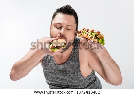 overweight man in tank top eating tasty hot dog isolated on white #1372418402