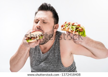 hungry overweight man in tank top eating hot dog isolated on white #1372418408