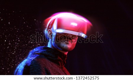 Model young man with beard in glasses of virtual reality on dark background. Augmented reality, future technology concept. VR. Neon light. #1372452575